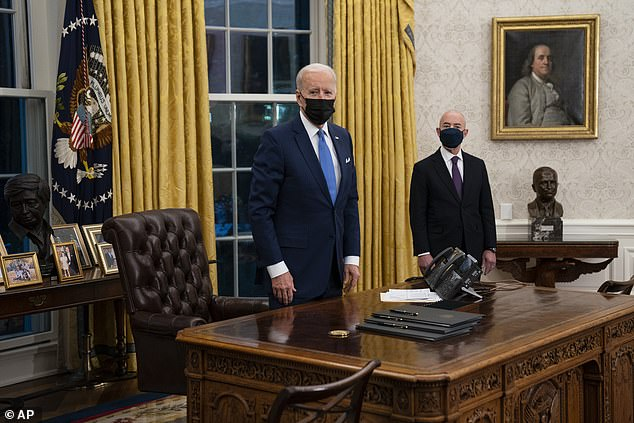 President Joe Biden (left) stands in the Oval Office alongside new Secretar of Homeland Security Alejandro Mayorkas (right) before signing three immigration-related executive orders early Tuesday evening