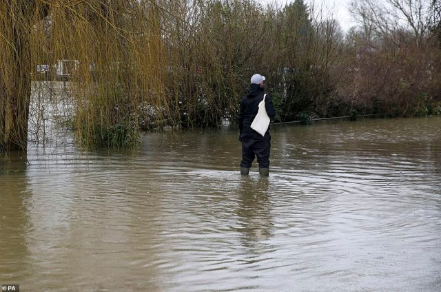 A man walks through flood water in Laleham-on-Thames, Surrey, today after the banks of the River Thames burst