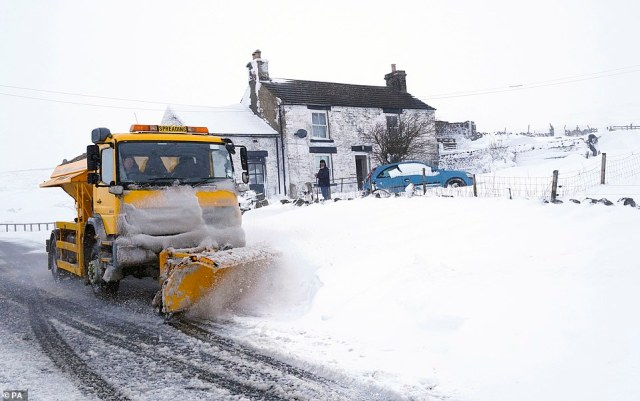 A snowplough making its way along a snow covered road in the village of Harwood in Teesdale, County Durham, today
