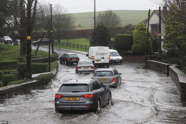 Cars make their way down a flooded road in Lisburn, Northern Ireland, this afternoon