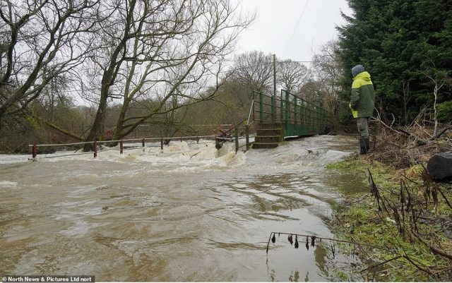 The River Wear has burst its banks causing flooding as a bridge is overwhelmed near Esh Winning in County Durham today