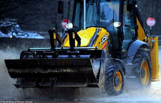 A JCB drives through floodwater in Sunderland this morning after the city was hit by heavy downpours overnight
