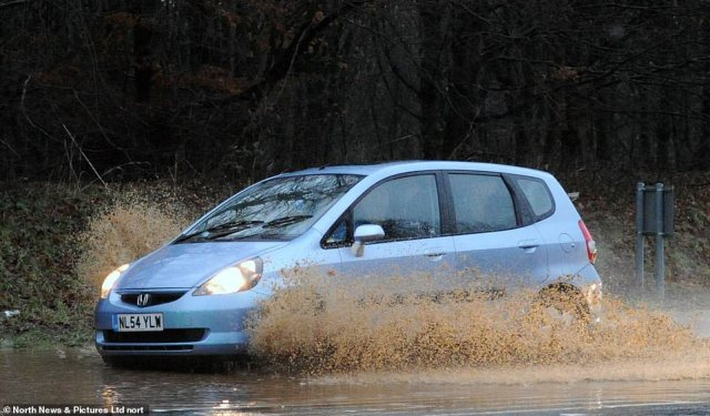 A car drives through floodwater in Sunderland today as the Environment Agency put out more than 200 alerts or warnings