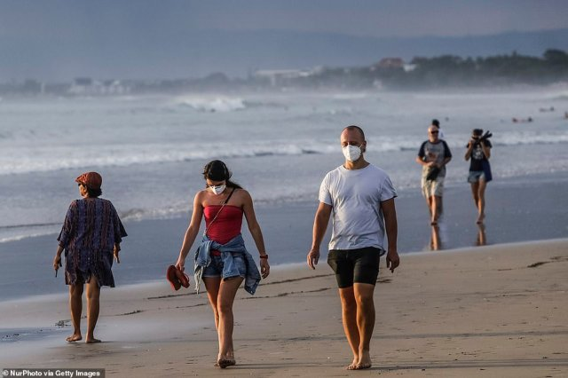 Bali's beaches are usually packed with international tourists all year round. Pictured are tourists on Kuta Beach in March, a month before Indonesia closed its foreign borders