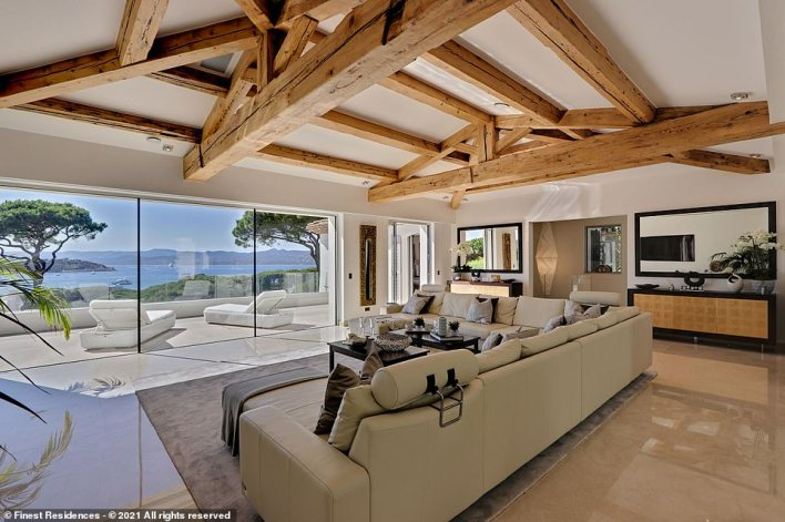 The living room, which according to the listing 'opens through large bay windows onto the main terrace and offers a breathtaking panoramic sea view, one of the most beautiful views from the entire domain of Les Parcs'