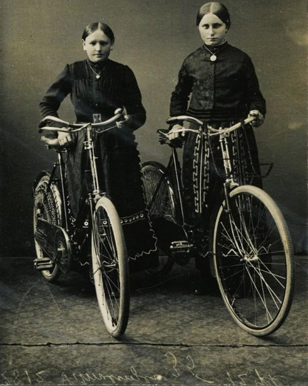 A classic 1900 studio photograph of two German girls proudly holding their bicycles