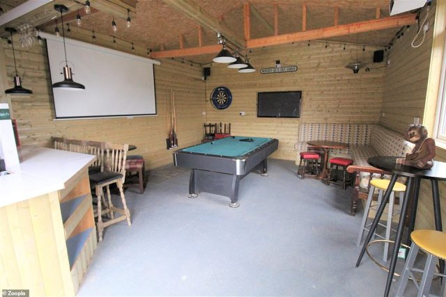 The perfect hideaway: Inside the outbuilding is  a games room with a movie screen and a pool table