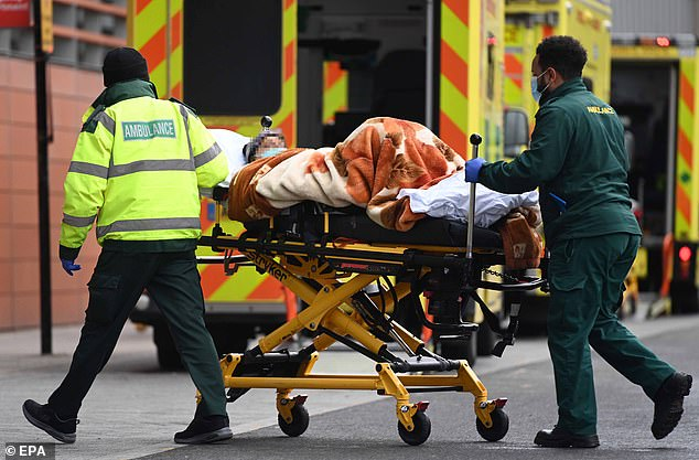 Ambulance staff bring a patient into the Royal London hospital in London today.Hospitals are still under immense strain and intensive care wards remain swamped despite the drop in coronavirus cases, an NHS boss warned tonight