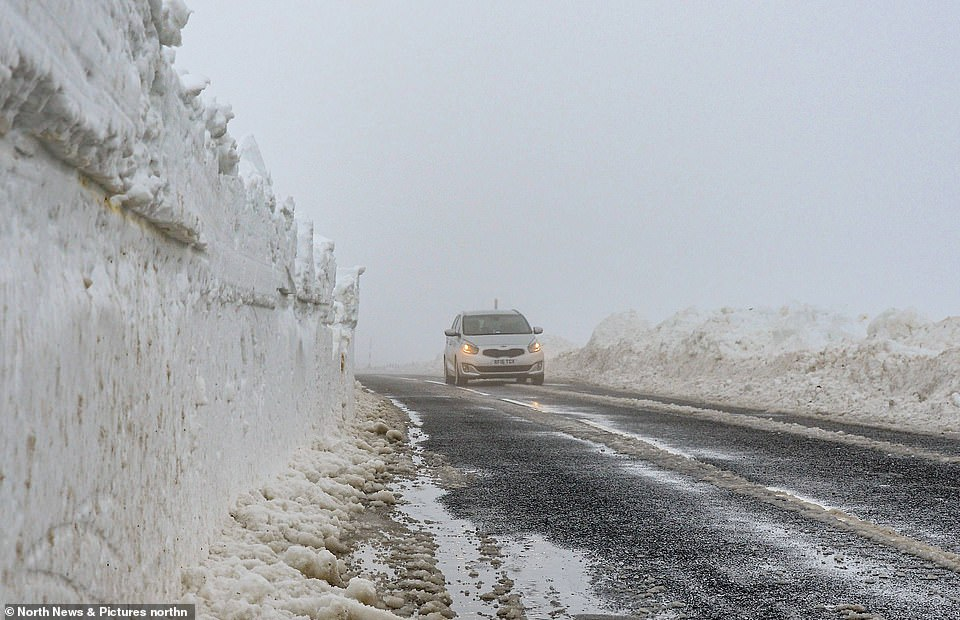 A motorist drives way through snow walls while on the Allendale to Nenthead road in Northumberlandyesterday