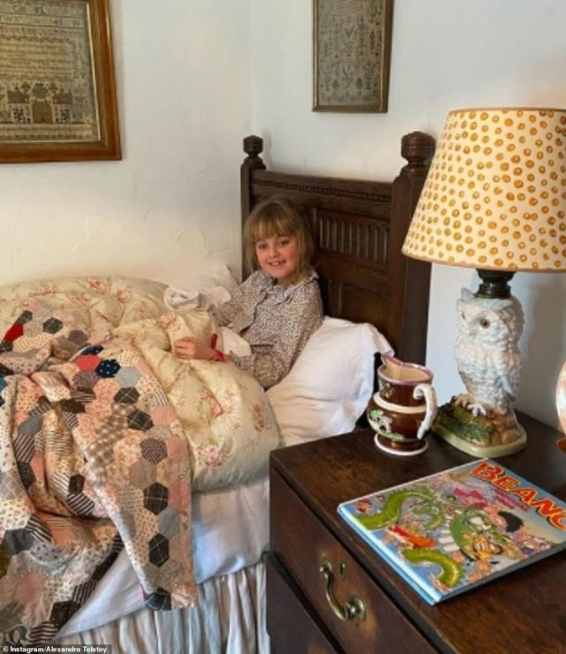 Old-fashioned goodness: Alexandra's daughter Maria tucked up in bed in one of the three bedrooms upstairs in the property
