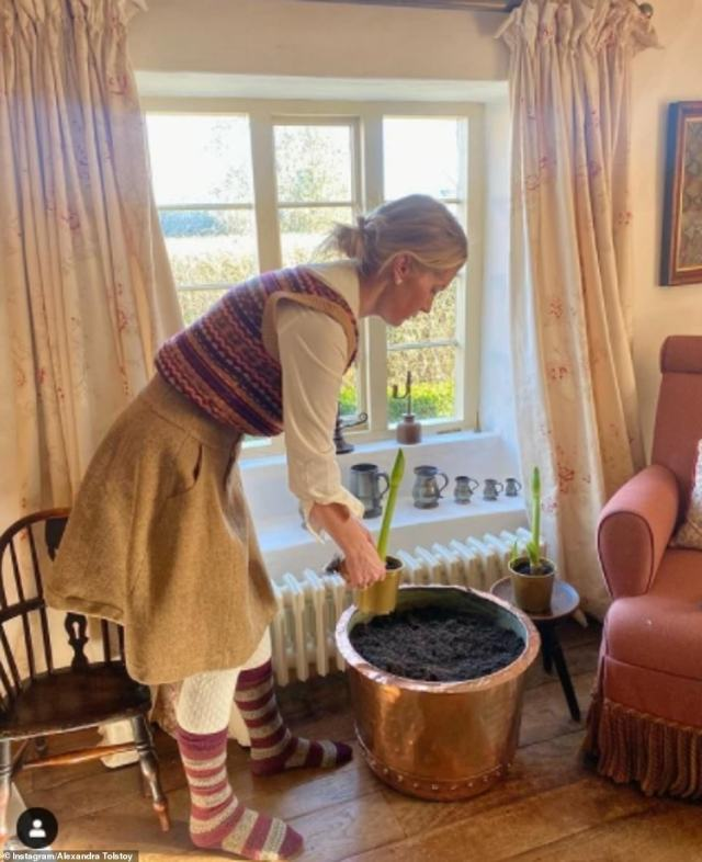 Pot plants: The socialite rearranges a flower in a large copper pot by a window looking out to the countryside