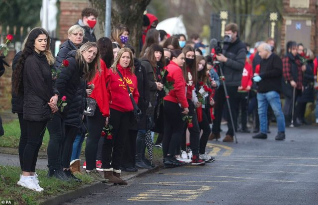 Hundreds lined the streets to pay their respects, throwing red roses as the funeral procession made its way to the crematorium