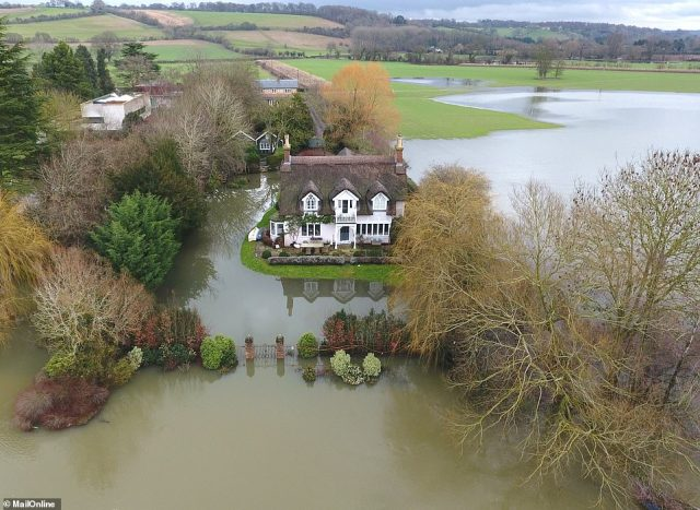 Russell Brand's £3.3million thatched cottage looked under threat today after the River Thames burst its banks in Berkshire