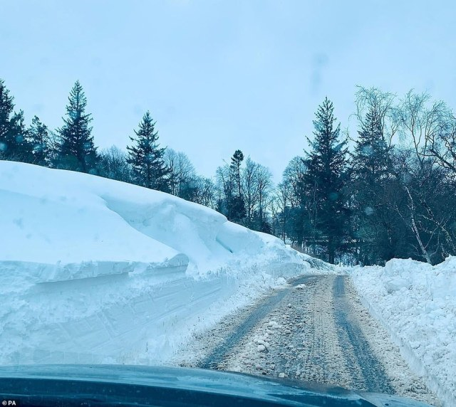 Pictured: An impressive build up of snow on two sides of a single-carriageway road near Tomatin in the Scottish Highlands