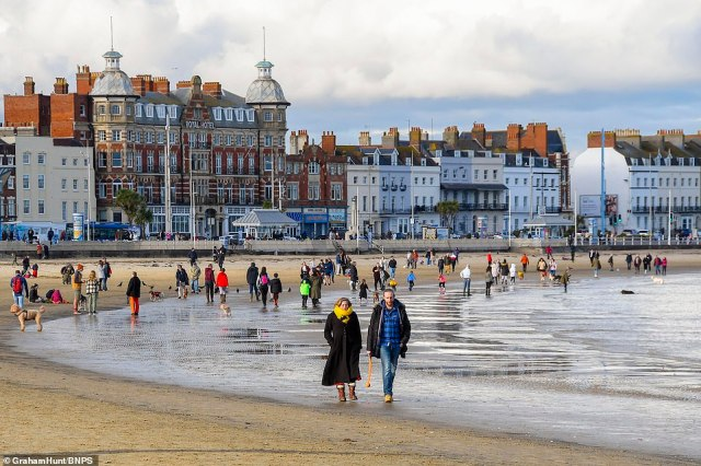 A beach in Weymouth, Dorset today as warm winter sun draws crowds to the seafront ahead of wintry weather tomorrow