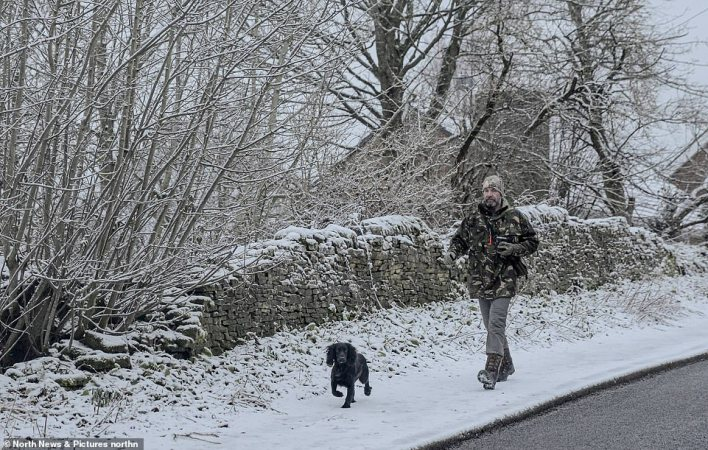 dog walker enjoys a walk in the snow in Castleside, County Durham this morning after overnight snowfall