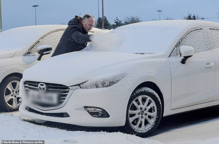 A motorist clears snow from a car in Consett, County Durham this morning after overnight snowfall