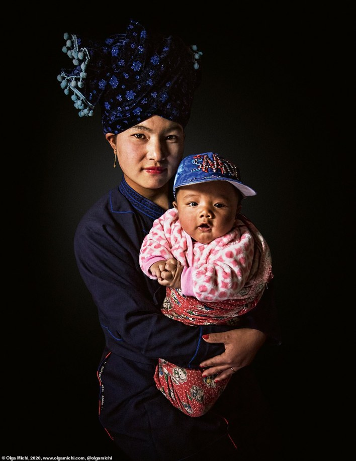 In this photo, traditional fashion meets more modern-day trends. A woman of the Tibeto-Burman Lisu ethnic group, who also reside in southwest China, is pictured with her child