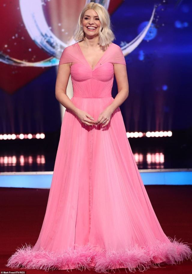 Stealing the spotlight: Host Holly was sure to steal focus amid the performances in her floor-length flowing pink chiffon gown which boasted off-the-shoulder sleeves, a fitted corset and an ostrich feather trim