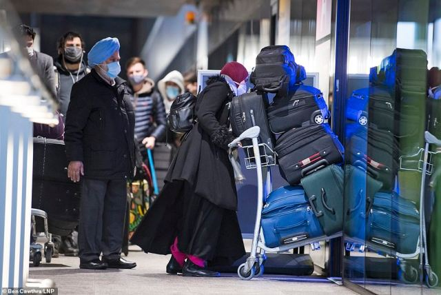 Travellers arriving in the UK queue outside a Covid testing centre on the first day of the government's hotel quarantine scheme. It is not clear if the people pictured will have to quarantine