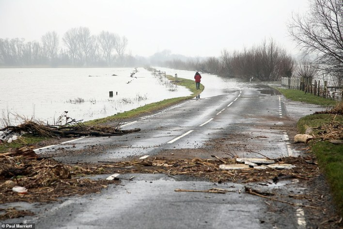 There are also 64 flood alerts, where people are warned to flooding could be possible, right across England. However there are no severe flood warnings - the most serious kind. Pictured:People out for a walk along a flooded road as melted snow and floodwater still covers the road from Thorney to Whittlesey, Cambridgeshire