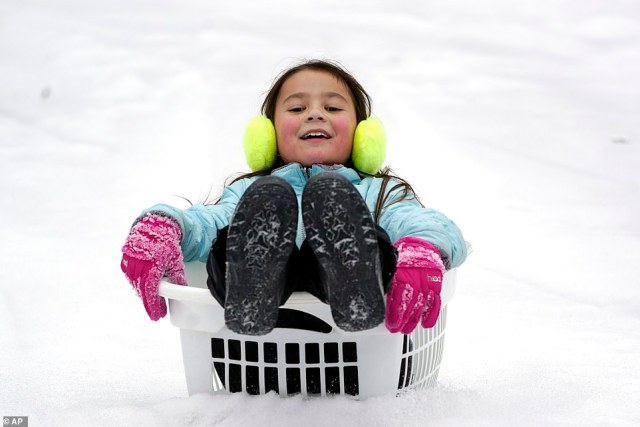 TENNESSEE:Peyton McKinney uses a laundry basket for a sled as she enjoyed the uncharacteristically snow condition on Monday