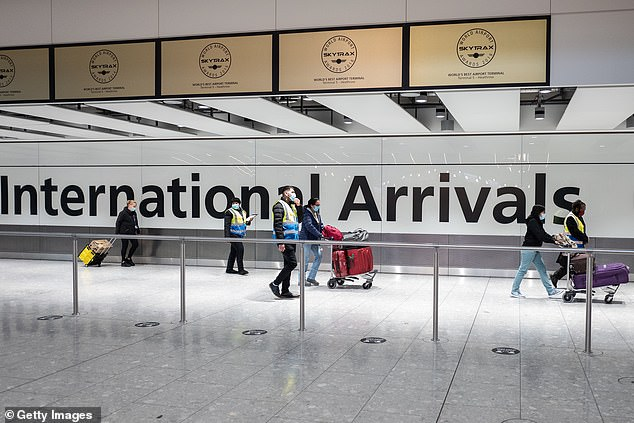 "Pictured: Travellers from one of the countries on the ""red list"" are escorted through the arrivals area of terminal 5 of Heathrow airport and onto a waiting coach, on February 16, 2021"