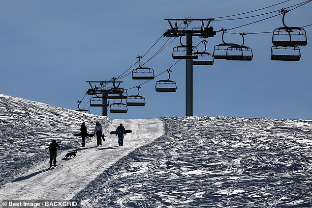 Pictured: Skiers and snowboarders walk up a hill next to closed ski lifts in Les Gets, France. The UK's largest ski holiday company has scrapped all trips this year and has offered its customers full refunds amid the coronavirus travel restrictions