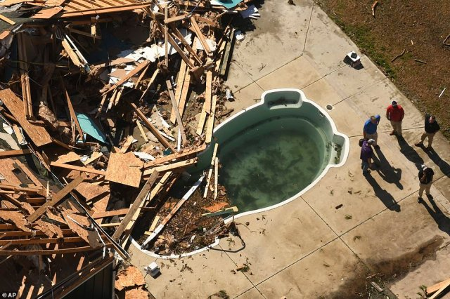 An aerial photo shows what is left of a home falling into the pool after a deadly tornado ripped through a seaside community in North Carolina