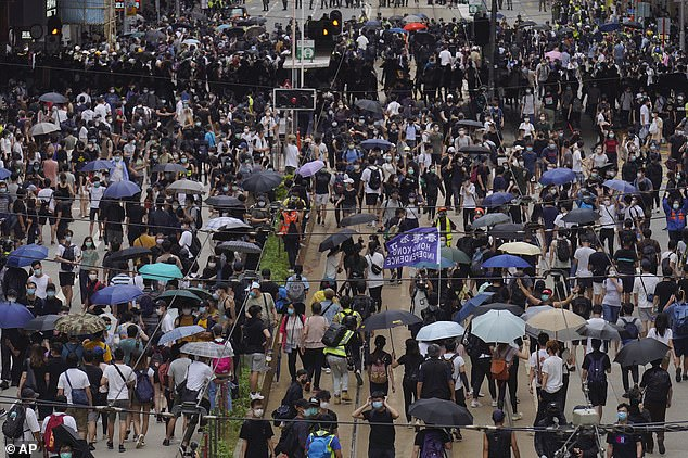 Pictured:Pro-democracy protesters march during a protest against Beijing's national security legislation in Hong Kong, Sunday, May 24, 2020