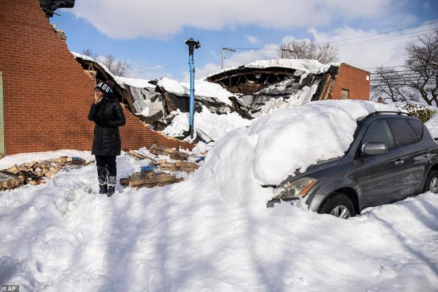 Chicago, Illinois:Jennifer Evans stands beside her car, which was damaged when the building collapsed during the storm