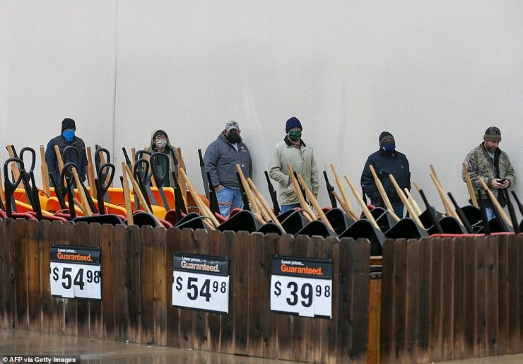 Customers wait outside at a Home Depot in Pearland, Texas to enter the store to buy supplies on February 17, 2021. The store has no power so is only letting one person at a time