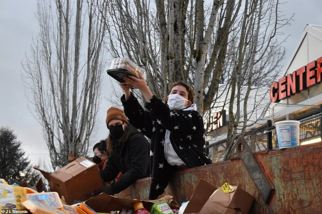 Residents hold aloft some of the food that was being tossed while many Oregonians are without power in the wake of winter storms