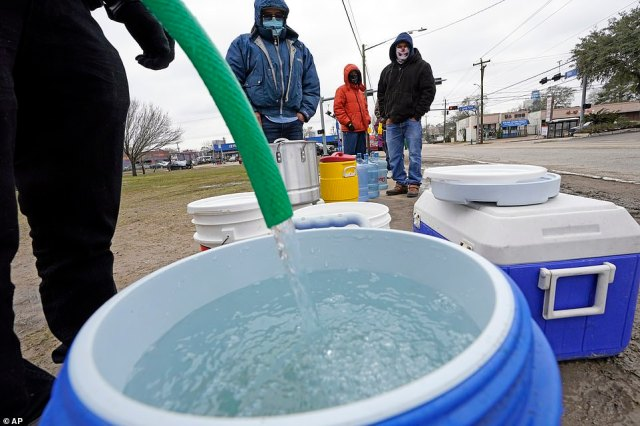 A water bucket is filled as others wait in near freezing temperatures to use a hose from public park spigot in Houston where residents are under a boil water order
