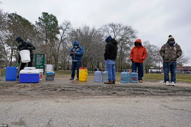 People wait in near freezing temperatures to fill water bottles and coolers with water from a public park spigot in Houston