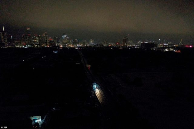Vehicles drive down East 7th Street as power outages continue to darken most of East Austin Wednesday night