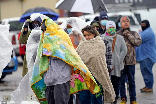 Texans covered in blankets wait in line for more than an hour to fill propane tanks to heat their homes in Houston on Wednesday