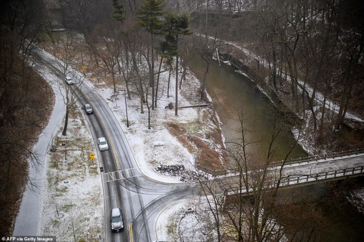 WASHINGTON, DC: Cars drive slowly on an icy road through Rock Creek Park in the Woodley Park neighborhood of Washington, DC, on Thursday