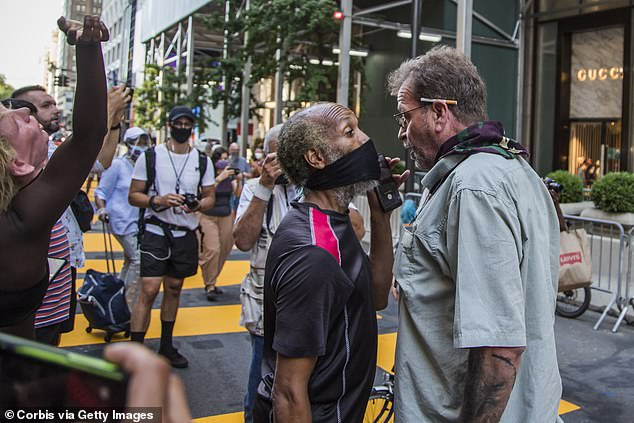 "Two men argue alongside the ""Black Lives Matter"" mural in front of the Trump Tower in New York last July. Researchers say partisanship is making Americans poorer and miserable"