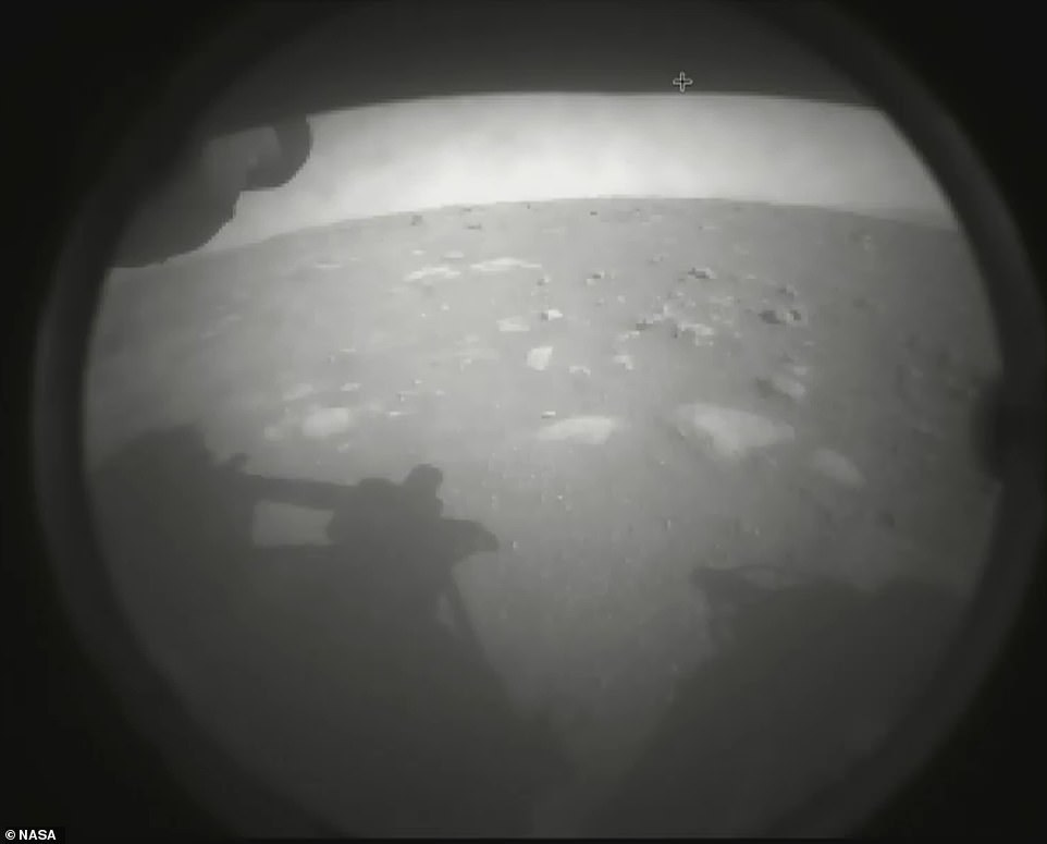 Perseverance touched down at the base of an 820ft-deep (250m) crater called Jezero, a former lake which was home to water 3.5 billion years ago. Pictured is one of the first images the rover sent back after landing on the Martian soil. Pictured, the first photo it beamed back to Earth after landing