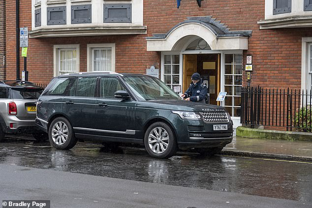 Britain's bravest traffic warden:Picture shows a Parking Warden putting a parking ticket on a royal protection officers Range Rover on a yellow line outside the King Edward V11 Hospital