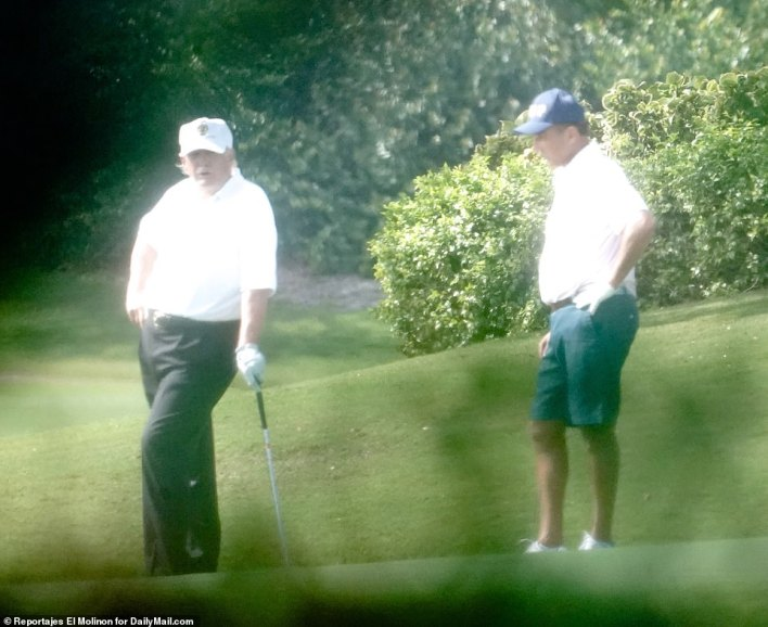 Trump (left) stands with an unknown golf partner on Thursday in Florida, one day after he did a number of interviews about the late Rush Limbaugh, who became a political ally and friend after Trump announced his bid for the White House in 2016