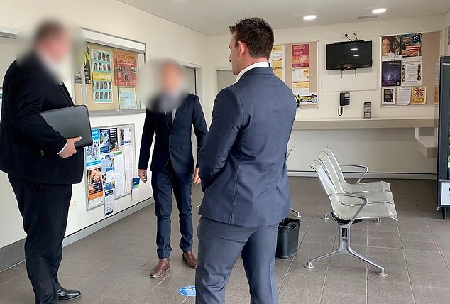 Feltham was charged with nine counts of publish etc false/misleading information to obtain advantage and participate criminal group contribute criminal activity. Pictured: Police with one of the accused men at a police station