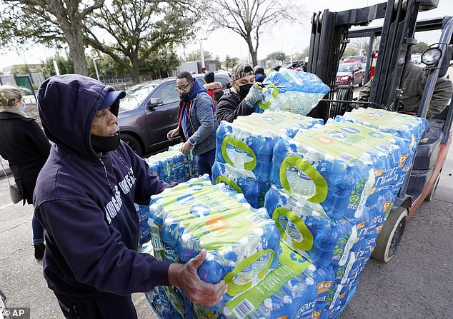 Houston, Texas:Donated water is distributed to residents, Thursday.A water crisis was also unfolding after Texas officials ordered 7 million people to boil tap water before drinking it