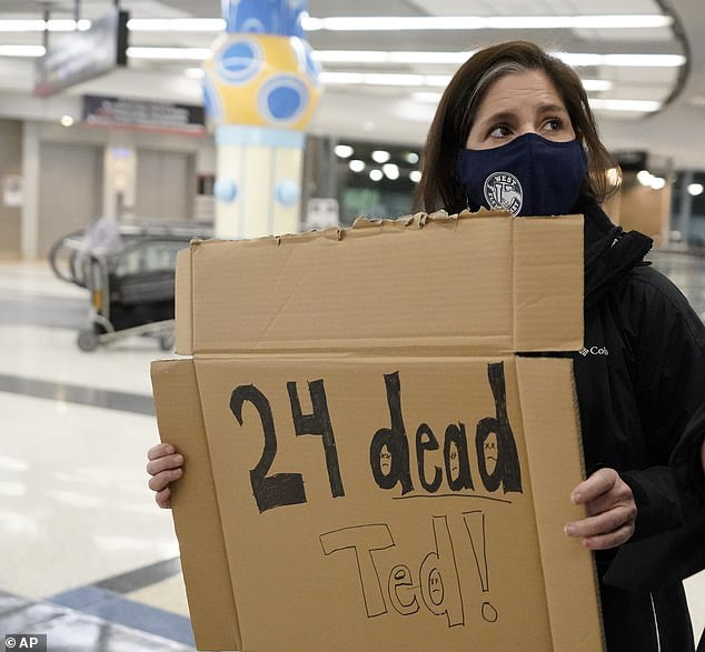 A protester, Mary Kay Hoffman, waited for Ted Cruz at Houston airport with a sign reminding him of the death toll from storms