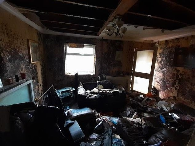The lounge room's ceiling has collapsed after suffering extensive water damage, with the walls also damage