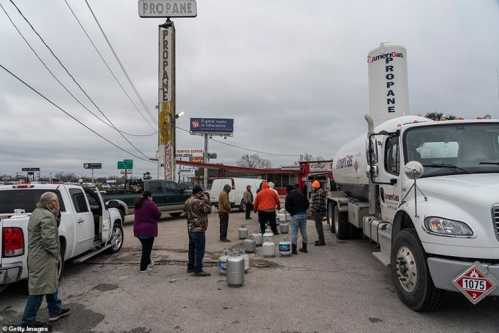 People line up at a propane gas station to refill their tanks after winter weather caused electricity blackouts