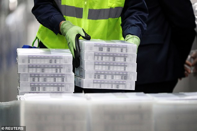 Pfizer exployees loaded vaccine doses into freezers during President Joe Biden's Michigan tour on Friday