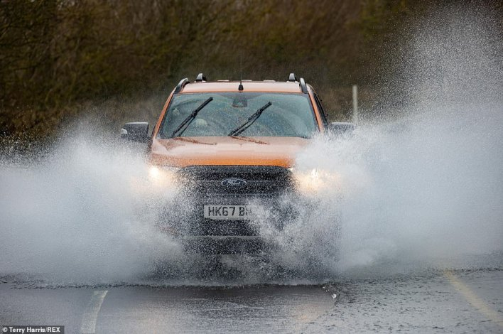 A car causes a splash as it drives through a flooded road in Sutton Gault, Cambridgeshire on Friday afternoon