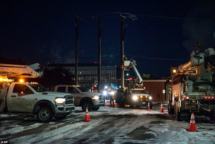 An Oncor Electric Delivery lineman crew works on repairing a utility pole that was damaged by the winter storm
